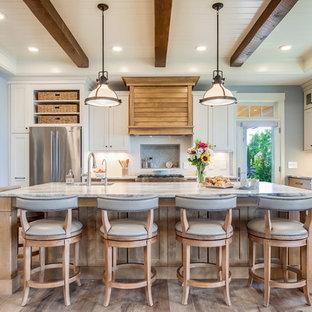 他の地域のビーチスタイルのおしゃれなキッチン (アンダーカウンターシンク、シェーカースタイル扉のキャビネット、中間色木目調キャビネット、白いキッチンパネル、シルバーの調理設備、無垢フローリング、茶色い床、白いキッチンカウンター) の写真