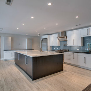 This is an example of a mid-sized beach style single-wall kitchen in Nashville with an undermount sink, flat-panel cabinets, white cabinets, quartzite benchtops, blue splashback, glass tile splashback, stainless steel appliances, linoleum floors and with island.