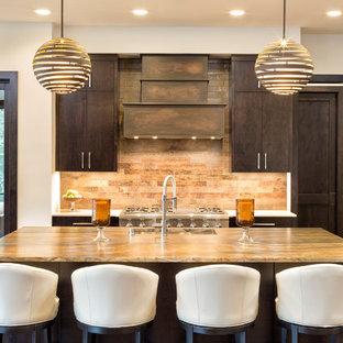 ミネアポリスのカントリー風おしゃれなアイランドキッチン (アンダーカウンターシンク、フラットパネル扉のキャビネット、濃色木目調キャビネット、茶色いキッチンパネル、シルバーの調理設備、濃色無垢フローリング、茶色い床、茶色いキッチンカウンター) の写真