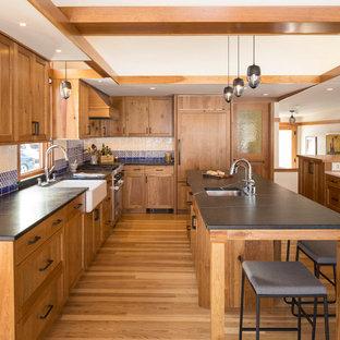 ミネアポリスのラスティックスタイルのおしゃれなキッチン (アンダーカウンターシンク、シェーカースタイル扉のキャビネット、中間色木目調キャビネット、青いキッチンパネル、パネルと同色の調理設備、淡色無垢フローリング、ベージュの床、黒いキッチンカウンター) の写真