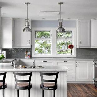 Transitional u-shaped kitchen in Vancouver with shaker cabinets, white cabinets, grey splashback, subway tile splashback, stainless steel appliances, dark hardwood floors and a peninsula.