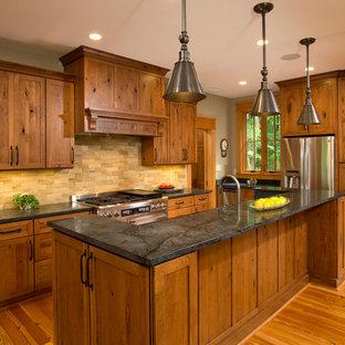 ワシントンD.C.のラスティックスタイルのおしゃれなアイランドキッチン (シェーカースタイル扉のキャビネット、中間色木目調キャビネット、ソープストーンカウンター、ベージュキッチンパネル、テラコッタタイルのキッチンパネル、シルバーの調理設備、無垢フローリング) の写真