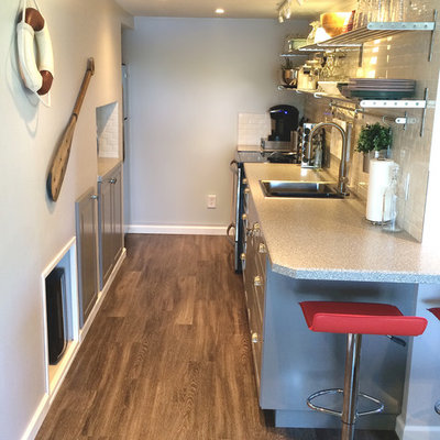 Example of a small trendy galley medium tone wood floor eat-in kitchen design in Other with a single-bowl sink, recessed-panel cabinets, gray cabinets, laminate countertops, white backsplash, subway tile backsplash, stainless steel appliances and no island