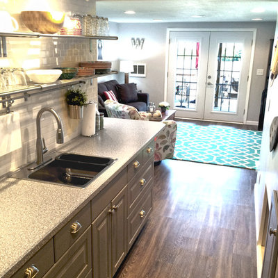 Example of a small trendy galley medium tone wood floor eat-in kitchen design in Other with a single-bowl sink, recessed-panel cabinets, gray cabinets, white backsplash, subway tile backsplash, stainless steel appliances and no island