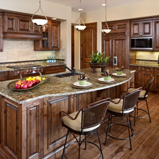 Inspiration for a mid-sized traditional l-shaped open plan kitchen in Denver with a double-bowl sink, raised-panel cabinets, medium wood cabinets, panelled appliances, medium hardwood floors, with island, brown floor, granite benchtops, beige splashback, stone tile splashback and multi-coloured benchtop.