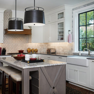 Mid-sized transitional enclosed kitchen pictures - Inspiration for a mid-sized transitional l-shaped dark wood floor and brown floor enclosed kitchen remodel in Grand Rapids with a farmhouse sink, white cabinets, quartz countertops, an island, glass-front cabinets, multicolored backsplash, multicolored countertops, marble backsplash and stainless steel appliances