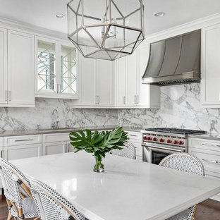 Mid-sized transitional eat-in kitchen designs - Example of a mid-sized transitional l-shaped dark wood floor eat-in kitchen design in Chicago with an undermount sink, white cabinets, solid surface countertops, white backsplash, stone slab backsplash, shaker cabinets and no island