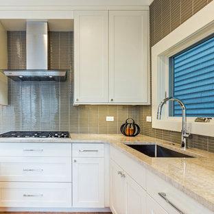 シカゴの中サイズのコンテンポラリースタイルのおしゃれなキッチン (アンダーカウンターシンク、シェーカースタイル扉のキャビネット、白いキャビネット、珪岩カウンター、グレーのキッチンパネル、ガラス板のキッチンパネル、シルバーの調理設備の、淡色無垢フローリング、黄色い床) の写真
