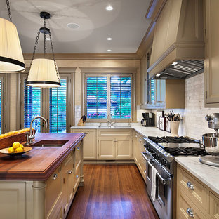 Traditional kitchen photos - Example of a classic kitchen design in Chicago with stainless steel appliances and wood countertops