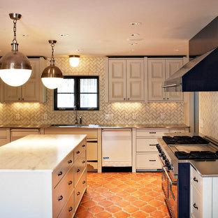 ダラスの地中海スタイルのおしゃれなキッチン (ステンレスカウンター、サブウェイタイルのキッチンパネル、落し込みパネル扉のキャビネット、白いキャビネット、ベージュキッチンパネル、カラー調理設備、テラコッタタイルの床、オレンジの床) の写真