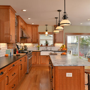 Inspiration for a timeless u-shaped medium tone wood floor and brown floor kitchen remodel in Cleveland with a farmhouse sink, recessed-panel cabinets, medium tone wood cabinets, white backsplash, subway tile backsplash, an island and gray countertops