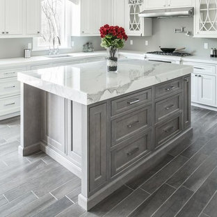 Example of a mid-sized trendy l-shaped ceramic tile eat-in kitchen design in Philadelphia with an undermount sink, marble countertops, stainless steel appliances, an island, shaker cabinets, white cabinets and gray backsplash