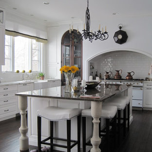 Mid-sized elegant u-shaped dark wood floor and brown floor eat-in kitchen photo in Detroit with a farmhouse sink, white backsplash, subway tile backsplash, white appliances, raised-panel cabinets, white cabinets, an island and white countertops