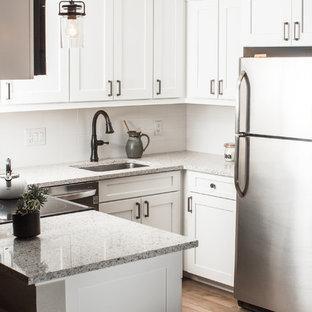 デンバーの小さいトランジショナルスタイルのおしゃれなキッチン (アンダーカウンターシンク、シェーカースタイル扉のキャビネット、白いキャビネット、御影石カウンター、白いキッチンパネル、セラミックタイルのキッチンパネル、シルバーの調理設備の、クッションフロア、茶色い床、ベージュのキッチンカウンター) の写真