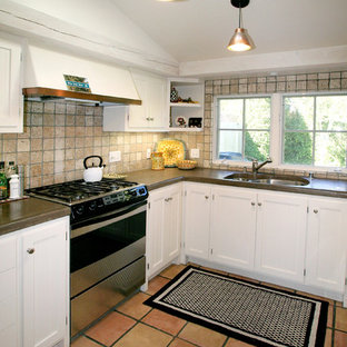 Mediterranean enclosed kitchen remodeling - Tuscan u-shaped terra-cotta floor enclosed kitchen photo in San Francisco with an undermount sink, recessed-panel cabinets, white cabinets, concrete countertops, beige backsplash, stone tile backsplash and stainless steel appliances