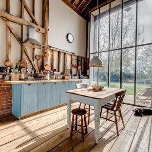 Idéer för att renovera ett mycket stort lantligt linjärt kök, med blå skåp och ljust trägolv