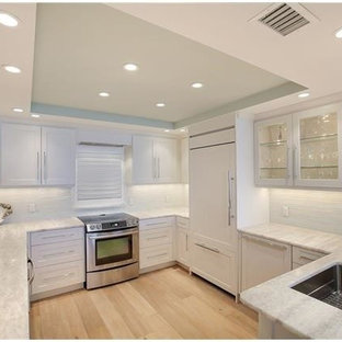 This is an example of a mid-sized beach style u-shaped separate kitchen in Miami with an undermount sink, shaker cabinets, white cabinets, onyx benchtops, white splashback, glass tile splashback, panelled appliances, light hardwood floors and no island.