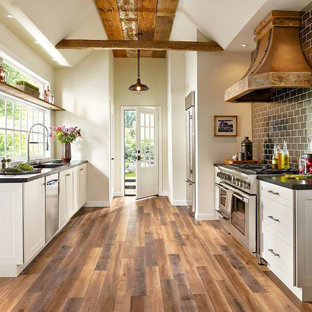 This is an example of a country kitchen in San Francisco with shaker cabinets, light wood cabinets, black splashback, metro tiled splashback, stainless steel appliances, medium hardwood flooring, no island and brown floors.