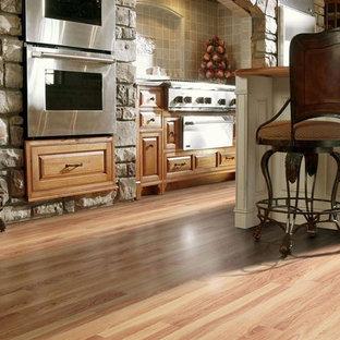 ポートランドの大きいカントリー風おしゃれなキッチン (アンダーカウンターシンク、レイズドパネル扉のキャビネット、淡色木目調キャビネット、コンクリートカウンター、グレーのキッチンパネル、石スラブのキッチンパネル、シルバーの調理設備の、ラミネートの床、茶色い床) の写真
