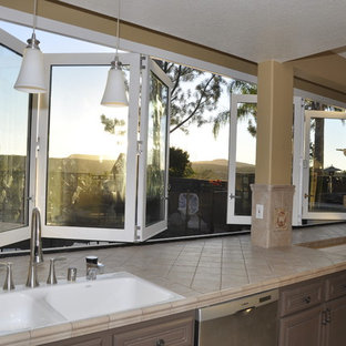 Idéer för avskilda, stora funkis linjära kök, med en dubbel diskho, öppna hyllor, vita skåp, kaklad bänkskiva, brunt stänkskydd och rostfria vitvaror