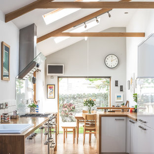 This is an example of a medium sized country u-shaped open plan kitchen in Other with flat-panel cabinets, white cabinets, wood worktops, white splashback, integrated appliances, medium hardwood flooring, a breakfast bar, brown floors, brown worktops and a built-in sink.