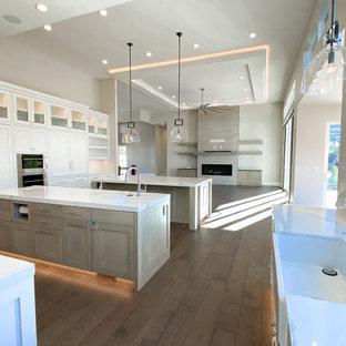 ソルトレイクシティの広いコンテンポラリースタイルのおしゃれなキッチン (エプロンフロントシンク、シェーカースタイル扉のキャビネット、白いキャビネット、クオーツストーンカウンター、白いキッチンパネル、大理石のキッチンパネル、シルバーの調理設備、濃色無垢フローリング、茶色い床、白いキッチンカウンター、格子天井) の写真