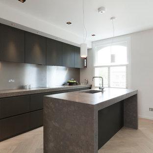 Foto di una cucina moderna di medie dimensioni con lavello da incasso, ante lisce, ante nere, top in pietra calcarea, paraspruzzi grigio, paraspruzzi con piastrelle di metallo, elettrodomestici in acciaio inossidabile, pavimento in legno massello medio e isola