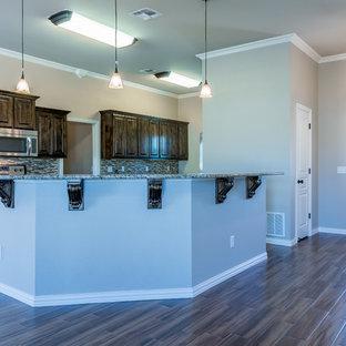 ダラスの広いヴィクトリアン調のおしゃれなキッチン (ベージュの床、アンダーカウンターシンク、レイズドパネル扉のキャビネット、濃色木目調キャビネット、御影石カウンター、グレーのキッチンパネル、ボーダータイルのキッチンパネル、シルバーの調理設備) の写真