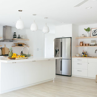 Contemporary open concept kitchen designs - Trendy l-shaped light wood floor and beige floor open concept kitchen photo in Sacramento with flat-panel cabinets, white cabinets, white backsplash, subway tile backsplash, stainless steel appliances and an island
