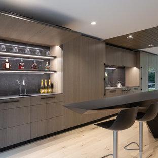 Modelo de cocina moderna con fregadero bajoencimera, armarios con paneles lisos, puertas de armario de madera oscura, suelo de madera clara, una isla, suelo beige y encimeras negras