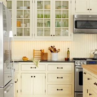 Klassische Küche mit Glasfronten, gelben Schränken, Arbeitsplatte aus Holz und Küchengeräten aus Edelstahl in Burlington
