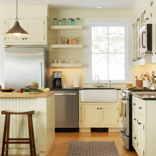Elegant kitchen photo in Burlington with a farmhouse sink, yellow cabinets, recessed-panel cabinets and stainless steel appliances