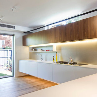Photo of a large modern galley open plan kitchen in Sydney with an integrated sink, flat-panel cabinets, medium wood cabinets, quartz benchtops, metallic splashback, metal splashback, black appliances, light hardwood floors and a peninsula.