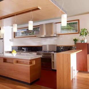 Photo of a contemporary l-shaped kitchen in Melbourne with a drop-in sink, flat-panel cabinets, medium wood cabinets, black splashback, mosaic tile splashback, white appliances, medium hardwood floors, with island, brown floor and white benchtop.