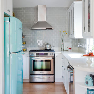 This is an example of an eclectic u-shaped kitchen in Vancouver with glass-front cabinets, white cabinets, grey splashback, subway tile splashback and coloured appliances.