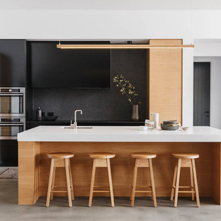 Design ideas for a contemporary galley kitchen in Other with an undermount sink, flat-panel cabinets, black cabinets, black splashback, stainless steel appliances, with island, grey floor and white benchtop.