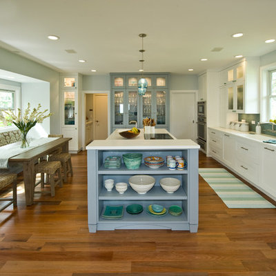 Inspiration for a mid-sized tropical medium tone wood floor eat-in kitchen remodel in Hawaii with an integrated sink, shaker cabinets, white cabinets, solid surface countertops, blue backsplash, glass tile backsplash, paneled appliances and an island