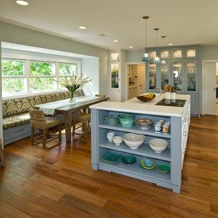 Exemple d'une arrière-cuisine exotique avec un placard à porte shaker, des portes de placard bleues, un plan de travail en surface solide, un électroménager encastrable et un îlot central.