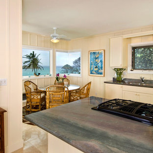 Mid-sized tropical u-shaped eat-in kitchen in Hawaii with an undermount sink, recessed-panel cabinets, beige cabinets, granite benchtops, stone slab splashback, stainless steel appliances and limestone floors.