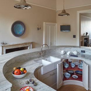 This is an example of a large traditional galley kitchen/diner in Wiltshire with a belfast sink, shaker cabinets, grey cabinets, marble worktops, grey splashback, stone slab splashback, stainless steel appliances, medium hardwood flooring and an island.