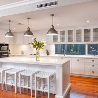 Design ideas for a transitional single-wall separate kitchen in Perth with shaker cabinets, white cabinets, window splashback, black appliances, medium hardwood floors, with island and orange floor.