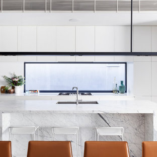 Inspiration for a contemporary galley kitchen in Melbourne with an undermount sink, flat-panel cabinets, white cabinets, window splashback, panelled appliances, with island, brown floor and grey benchtop.