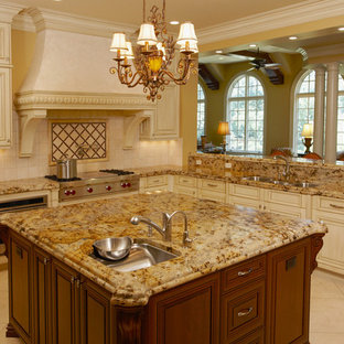 Пример оригинального дизайна: угловая кухня-гостиная среднего размера в классическом стиле с тройной раковиной, фасадами с выступающей филенкой, белыми фасадами, столешницей из гранита, бежевым фартуком, фартуком из керамической плитки, техникой из нержавеющей стали, полом из керамической плитки и островом
