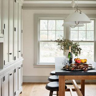 ニューヨークの中くらいのビーチスタイルのおしゃれなキッチン (エプロンフロントシンク、シェーカースタイル扉のキャビネット、グレーのキャビネット、大理石カウンター、グレーのキッチンパネル、石タイルのキッチンパネル、シルバーの調理設備、淡色無垢フローリング、オレンジの床) の写真