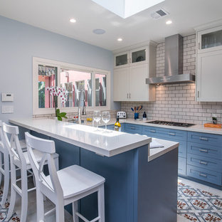 Design ideas for a mid-sized transitional u-shaped separate kitchen in Los Angeles with shaker cabinets, blue cabinets, white splashback, subway tile splashback, a peninsula, multi-coloured floor, white benchtop, an undermount sink, limestone benchtops, stainless steel appliances and ceramic floors.