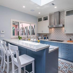 Inredning av ett klassiskt avskilt, mellanstort vit vitt u-kök, med skåp i shakerstil, blå skåp, vitt stänkskydd, stänkskydd i tunnelbanekakel, en halv köksö, flerfärgat golv, en undermonterad diskho, bänkskiva i kalksten, rostfria vitvaror och klinkergolv i keramik