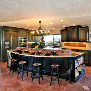 Eat-in kitchen - large traditional l-shaped porcelain floor and brown floor eat-in kitchen idea in San Diego with an undermount sink, recessed-panel cabinets, green cabinets, granite countertops, beige backsplash, ceramic backsplash, stainless steel appliances and an island