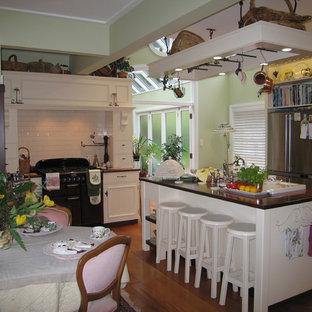 ウェリントンの中サイズのカントリー風おしゃれなキッチン (レイズドパネル扉のキャビネット、白いキャビネット、木材カウンター、白いキッチンパネル、サブウェイタイルのキッチンパネル、シルバーの調理設備の、無垢フローリング、緑の床、茶色いキッチンカウンター) の写真