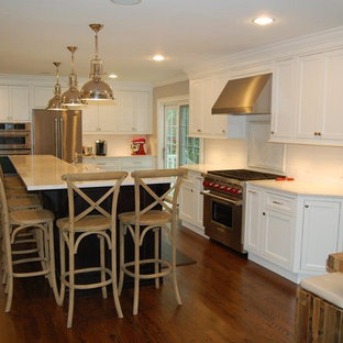 Inspiration for a mid-sized eclectic l-shaped dark wood floor eat-in kitchen remodel in New York with a farmhouse sink, shaker cabinets, white cabinets, quartz countertops, white backsplash, stainless steel appliances and an island