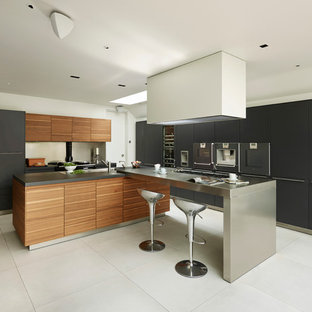 Inspiration for a contemporary kitchen in Cheshire with flat-panel cabinets, medium wood cabinets, metallic splashback, integrated appliances and an island.